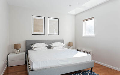 a newly furnished room with a bed, nightstands, and two framed paintings above the bed