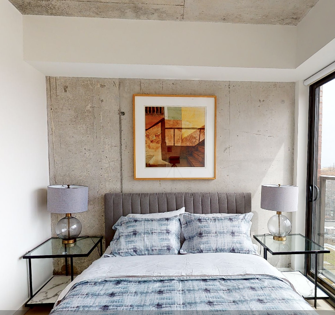 a bedroom with a concrete wall, bedside table, and warm colored painting above the bed