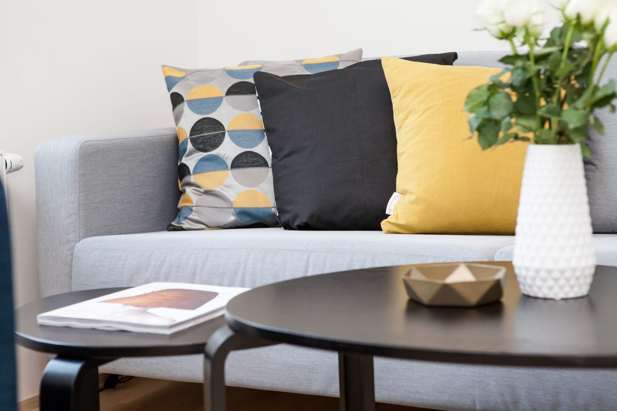 A small space living room with color coordinated throw cushions and a small coffee table with plant and ashtray.
