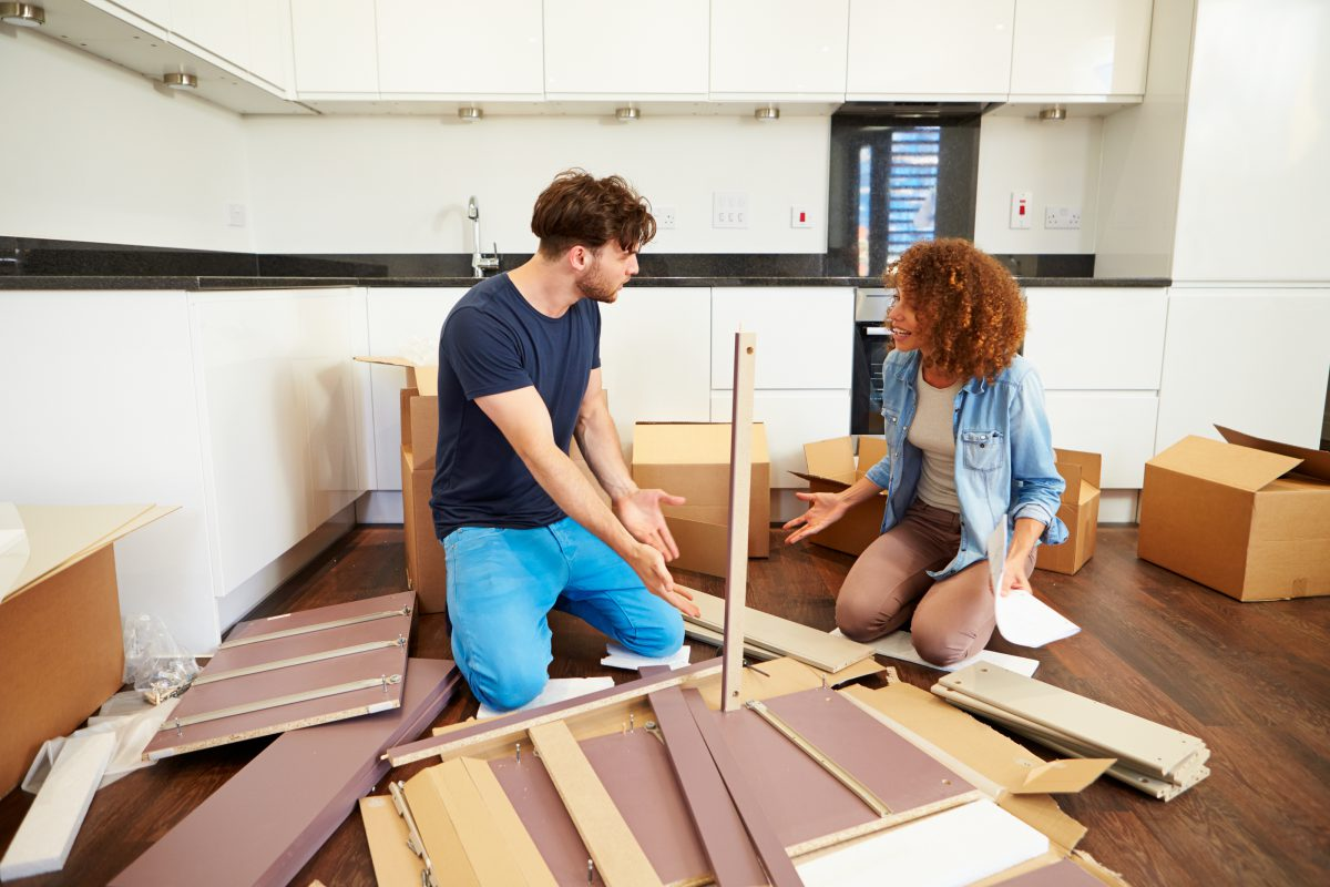 Couple assembling furniture together