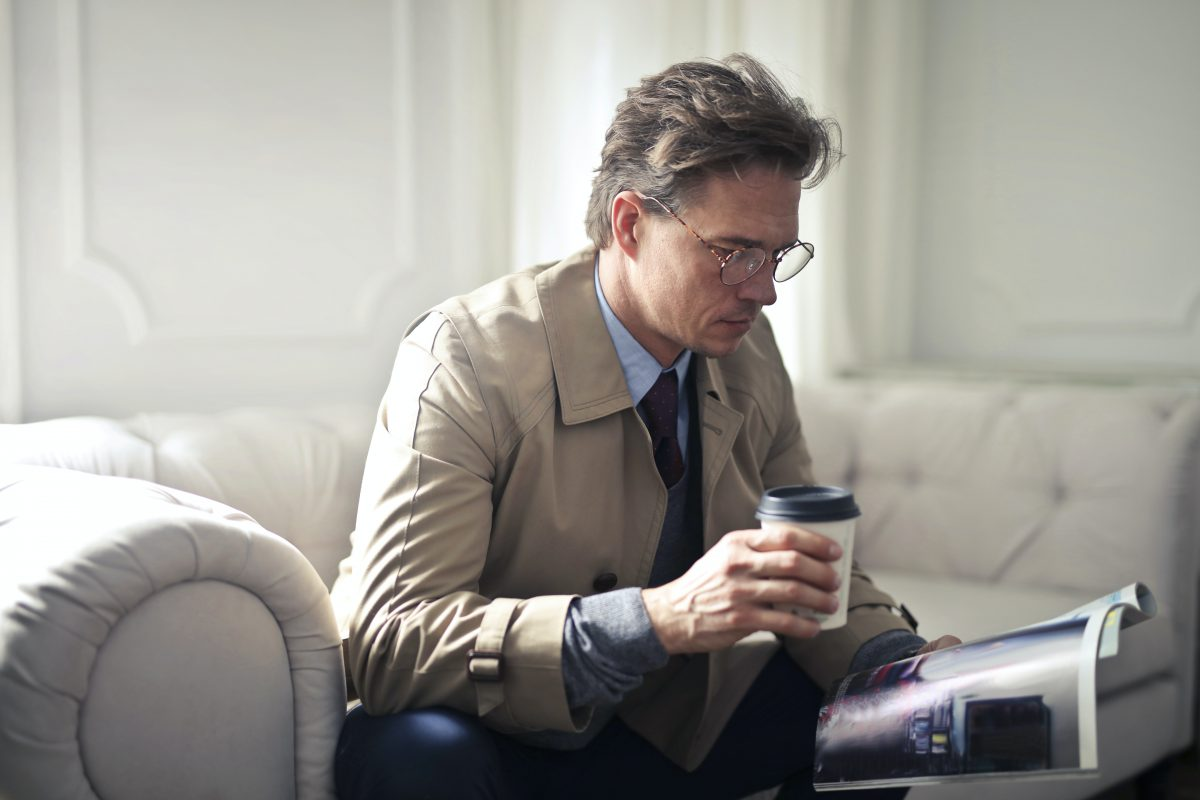 A middle aged man with a takeaway coffee sits on a beige leather couch and reads a magazine calmly.
