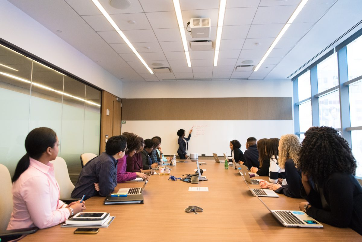 A group of people sit around a long conference table while someone gives a presentation. Bright fluorescent lights hang on the ceiling above.