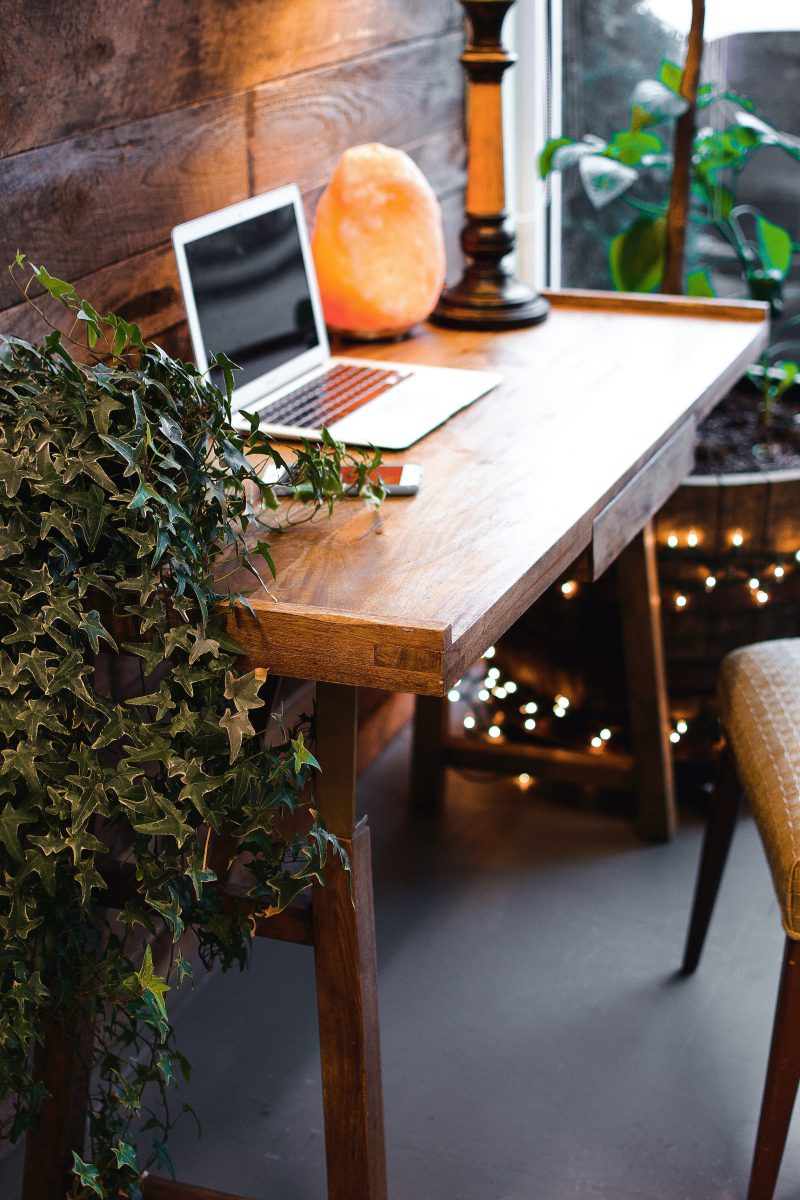 a wood desk with laptop and salt lamp and plant