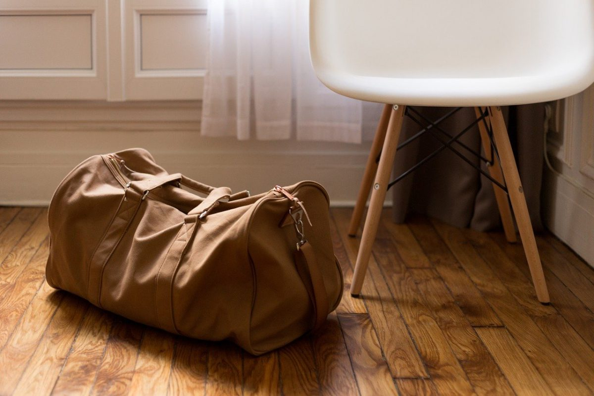 a tan duffel bag on the ground beside a white chair