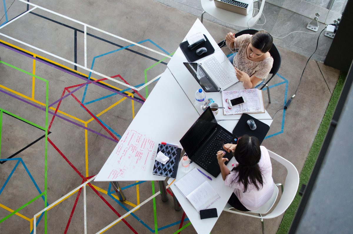 two women sitting in chairs using laptop computers photographed from above